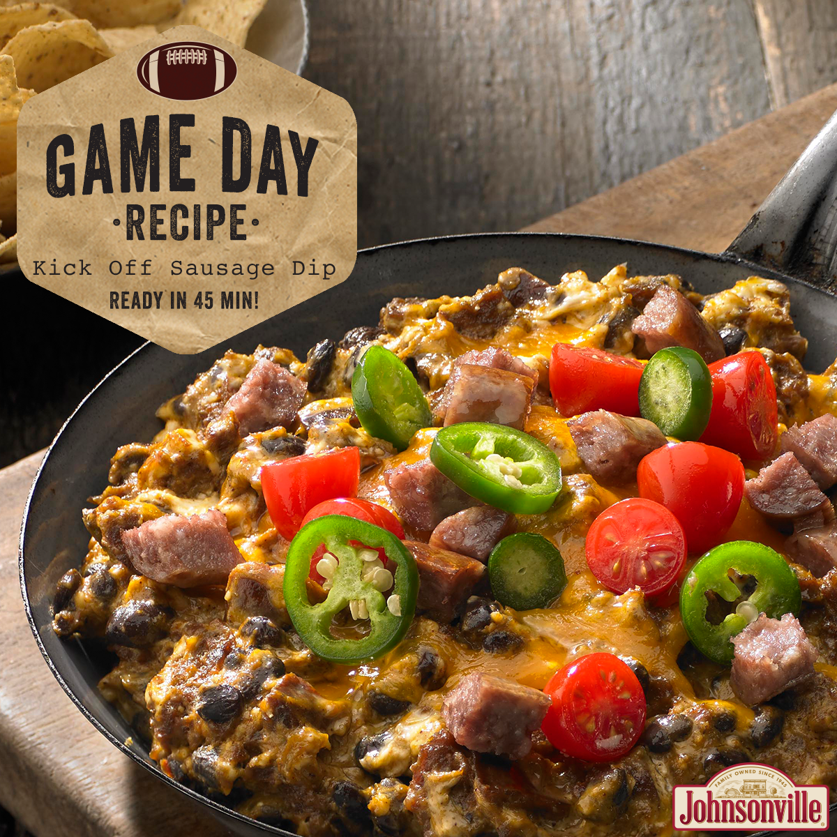 Sausage dip, including sausage, jalapenos, cheese and tomatoes, cooking in a skillet