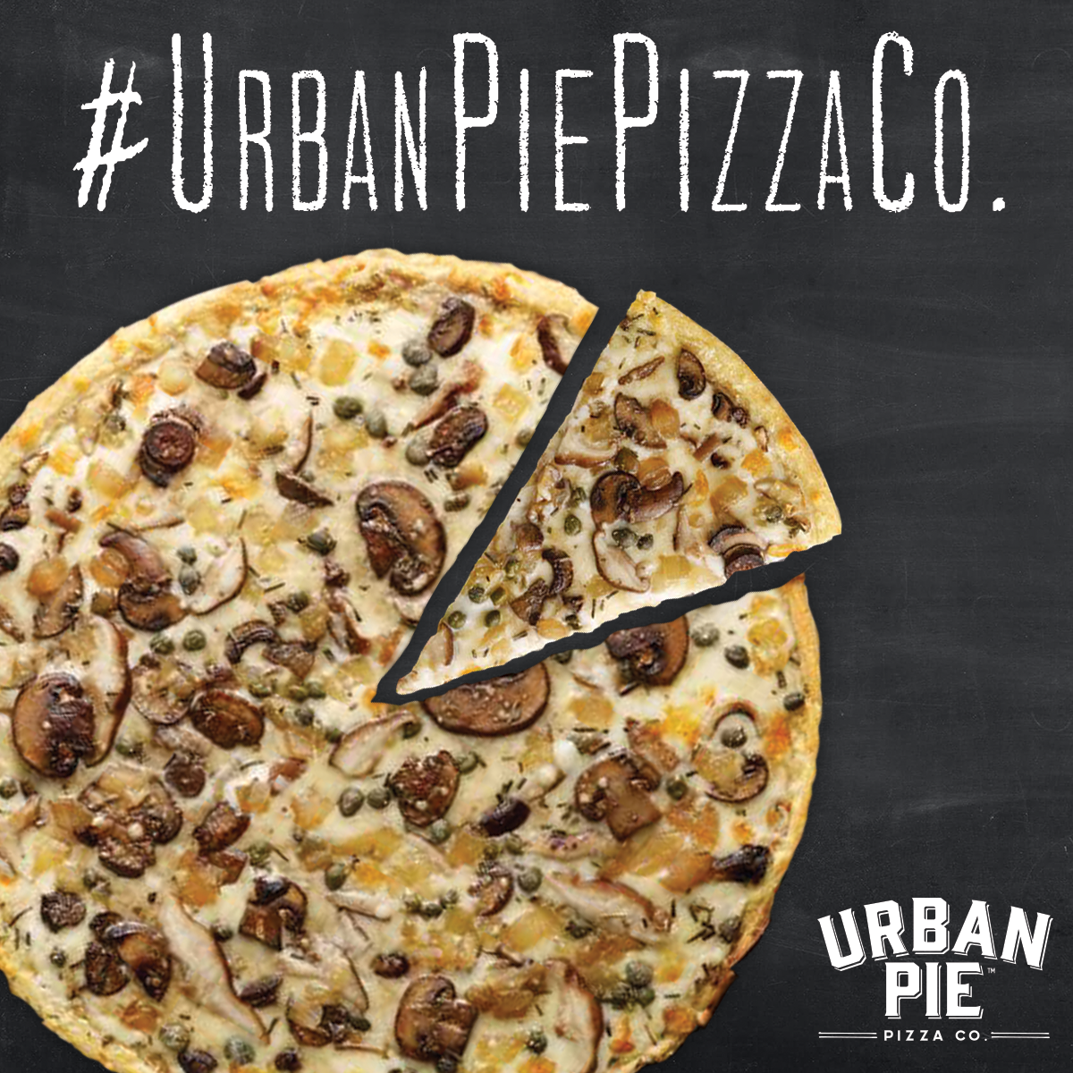 "In front of a slate gray background sits a cooked Urban Pie pizza topped with cheese, mushrooms, and onions. One slice is cut out from the pie and sitting separate. Across the top of the picture reads ""#UrbanPiePizzaCo"""