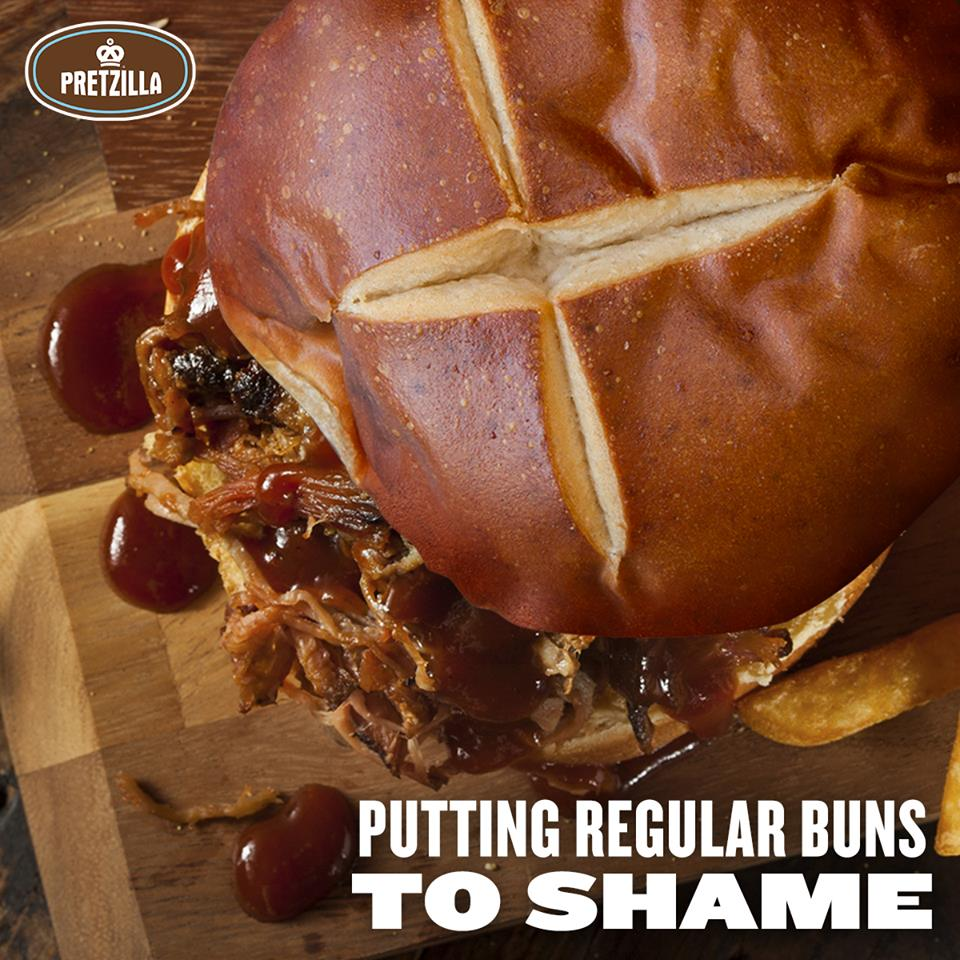 "an arial view of pretzilla burger bun on top of a barbecue pulled pork sandwich. the logo is in the top left corner and the copy in the bottom right corner reads, ""putting regular buns to shame"""