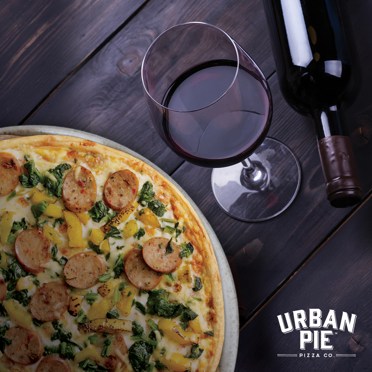 Half off picture sits a cooked Urban Pie pizza topped with chicken sausage, yellow peppers, and cheese. Next to the pizza is a stemmed glass of red wine sitting on a dark wood background with a bottle of wine next to it on its side.