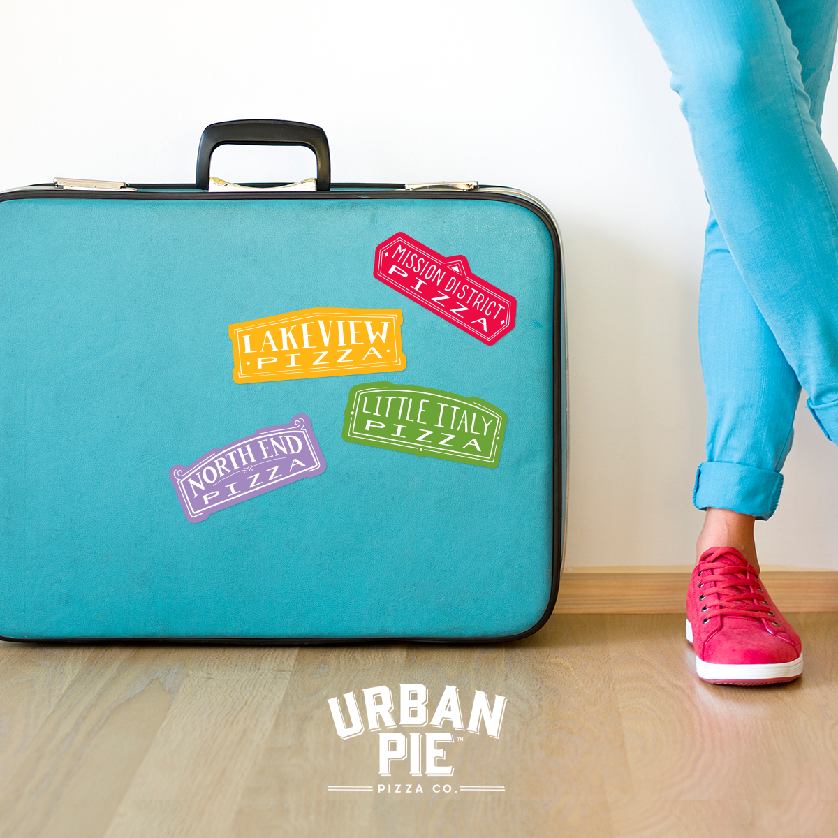 "A light blue suitcase sits on a light wood floor. On the suitcase there are multiple stickers: a red one reading ""Mission District Pizza,"" a purple one reading ""North End Pizza,"" a green one reading ""Little Italy Pizza,"" and a yellow one reading ""Lakeview Pizza."" Standing next to the suitcase is a pair of crossed legs wearing light denim and red tennis shoes."
