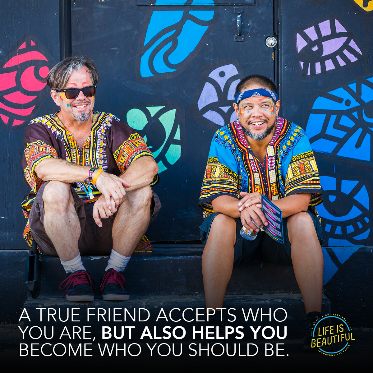 "Two men sit in front of a navy blue wall painted with different versions of artistic renderings of human eyes in bright colors. The men are wearing brightly colored tunics and have painted their faces with red, blue and yellow. Text on the image reads ""A true friend accepts who you are, but also helps you become who you should be."" In the bottom right corner sits the Life is Beautiful festival logo."