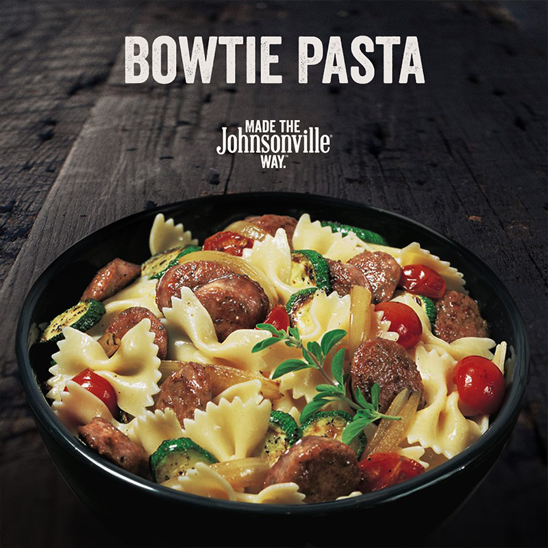 A bowl of bowtie pasta filled with sausage, tomatoes and zucchini for Johnsonville