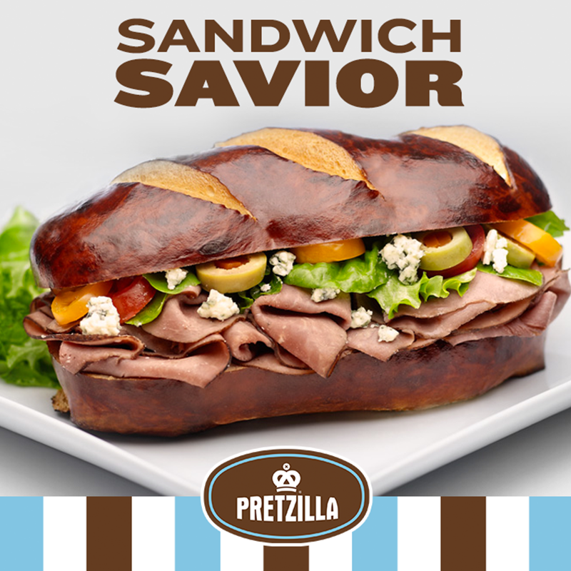 "a large sub sandwich on a pretzilla pretzel bun stacked high with roast beef, cheese, peppers and lettuce. the copy reads ""sandwich savior"""