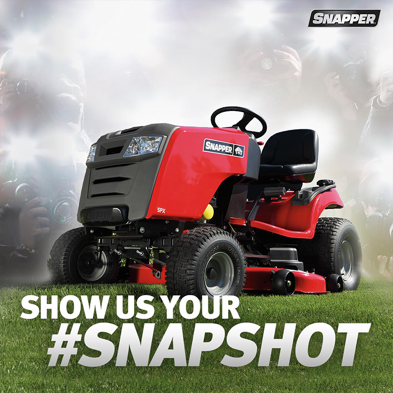Red Snapper riding lawn mower sitting on green turf surrounded by the lights of camera flashes. Text on image reads Show Us your #shapshot.