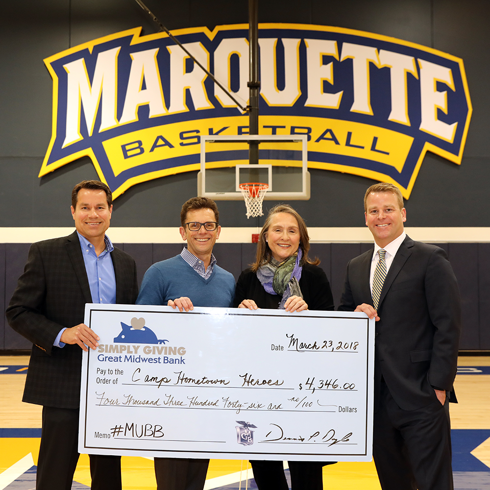 "Great Midwest Bank President and CEO Dennis Doyle stands with Great Midwest Bank Senior Vice President Jon Reetz and Marquette Basketball Coach Steve Wojciechowski and Camp Hometown Heroes Director of Outreach Deb Paschke and Doyle, Reetz, and  Wojciechowski present Paschke with an oversized ""Simply Giving"" branded check made out to Camp Hometown Heroes in the amount of $4346.00"